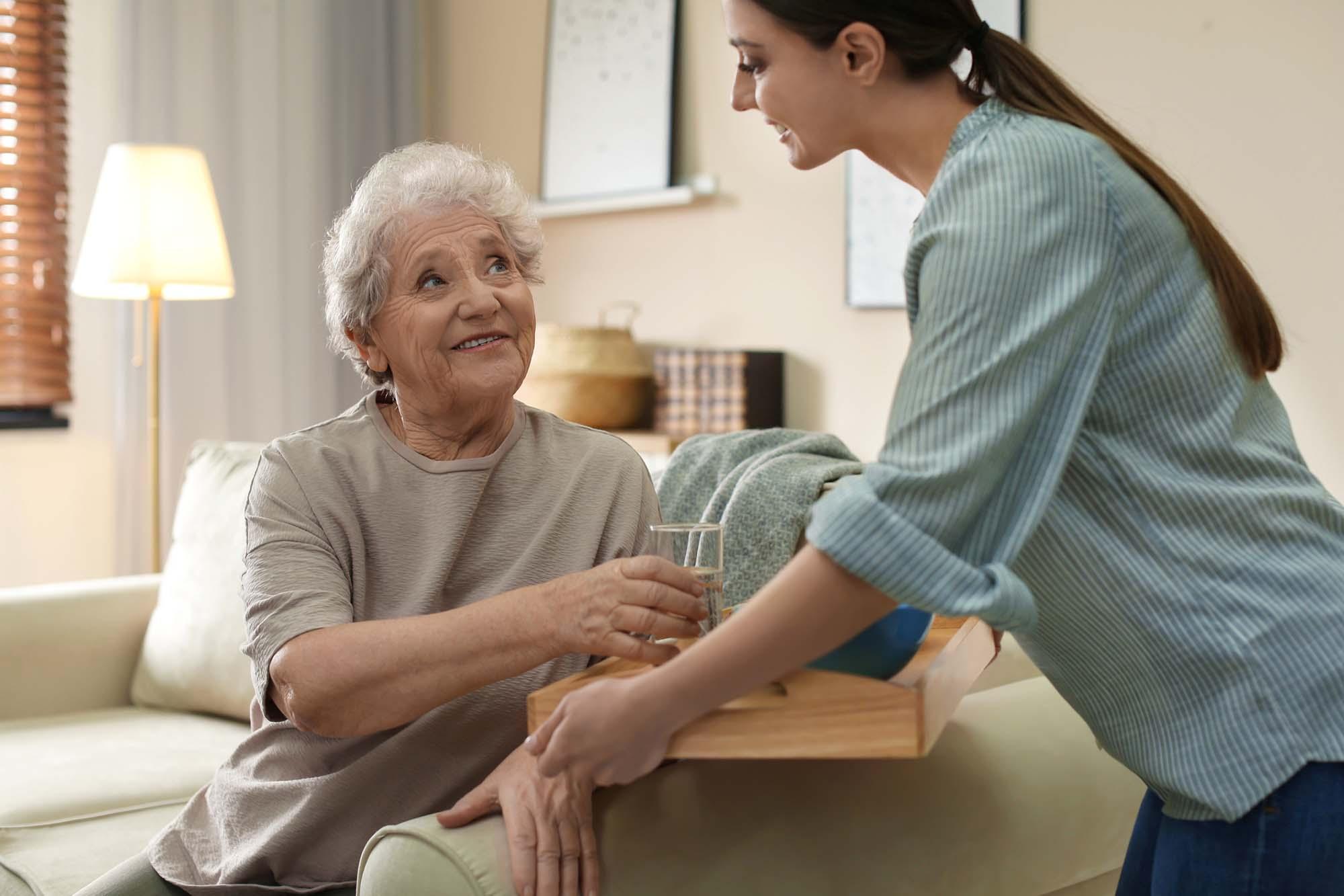 Carer offering elderly woman water